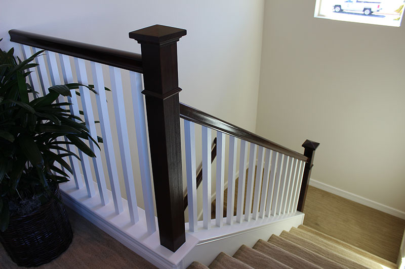 Bow newel post with stain grade handrail